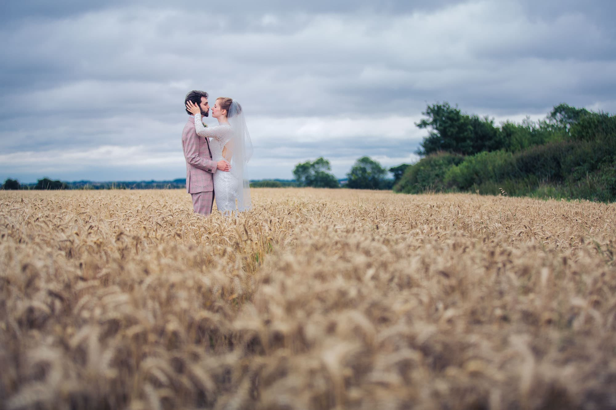 Romantic bride and groom in cornfield wedding photograph